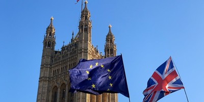 Union Jack and EU flags fly over the London House of Commons