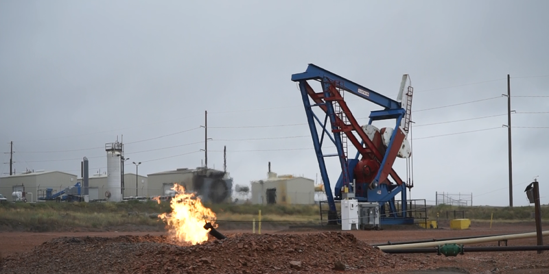 A%20gas%20flare%20burns%20by%20a%20rig